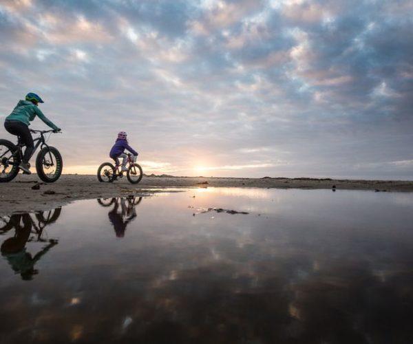 People riding bikes on coast